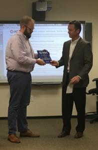 Jason McFarland presents an award to Brad Green, IADC Manufacturing Record Book Subcommittee Chairman
